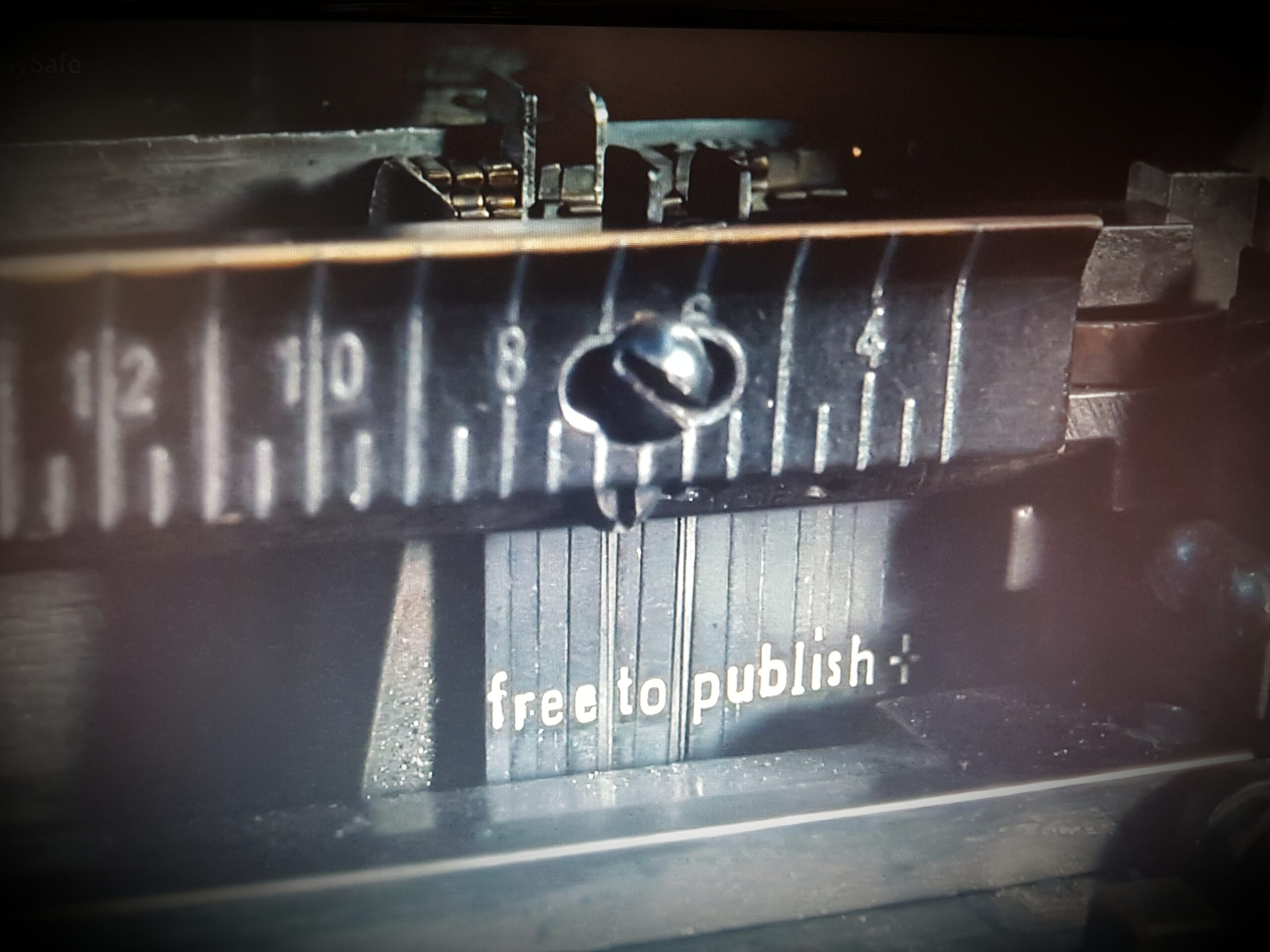 "A still frame from the film ""The Post"" showing an old printing press, loaded with type blocks which say ""free to publish"""