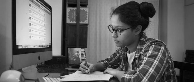 Photograph of a girl doing homework at a computer