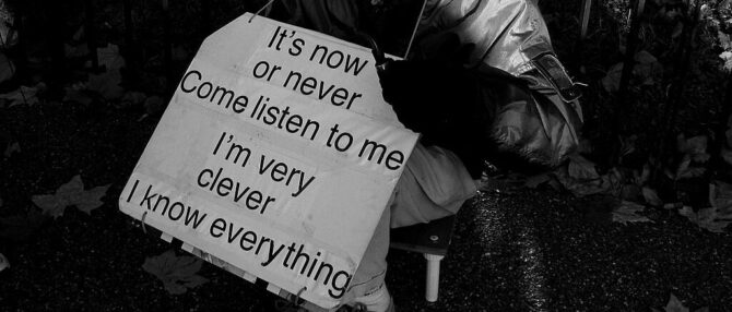 """Man holding up a sign at Speaker's Corner that says """"It's now or never, come listen to me, I'm very clever, I know everything"""""""